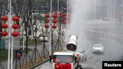 武汉工人在街道上喷洒消毒药水以抗击新冠疫情。(2020年2月10日)