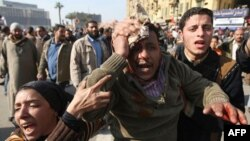 A wounded demonstrator is evacuated from Cairo's main square, Egypt, Wednesday, Feb.2, 2011. Several thousand supporters of President Hosni Mubarak, including some riding horses and camels and wielding whips, clashed with anti-government protesters as Egy