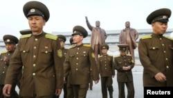 朝中社发布的照片显示, 在朝鲜建军节,朝鲜军人走在前领导人人今日成和金正日的青铜像前面(2017年4月25日)