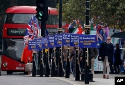 FILE - Brexit opponents display their posters in front of Parliament in London, Oct. 23, 2019.