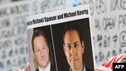 (资料照) 加拿大抗议人士举着加拿大商人迈克尔·斯帕弗(Michael Spavor)和加拿大前外交官康明凯(Michael Kovrig)的头像的标语,抗议中国政府任意拘押这两位加拿大公民。(美联社)