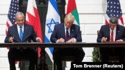 Premijer Izraela Benjamin Netanjahu, predsednik SAD Donald Tramp i Minstar spoljnih poslova UAE Abdulah bin Zajed (s leva) potpisuju Abrahamov sporazum, o normalizaciji odnosa između Izraela i nekih njegovih suseda na Bliskom istoku (Foto: Reuters/Tom Brenner)
