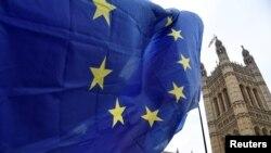Seorang pengunjuk rasa anti-Brexit mengibarkan bendera Uni Eropa di seberang Gedung Parlemen di London, Inggris, 10 Desember 2018. REUTERS / Toby Melville - RC1A156F3990