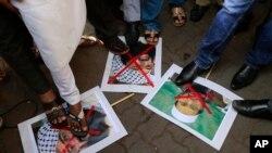 بھارت میں ہونے والے ایک مظاہرے کے دوران لوگ مسعود اظہر اور حافظ سعید کی تصاویر پر پاؤں رکھے کھڑے ہیں۔ (فائل فوٹو)