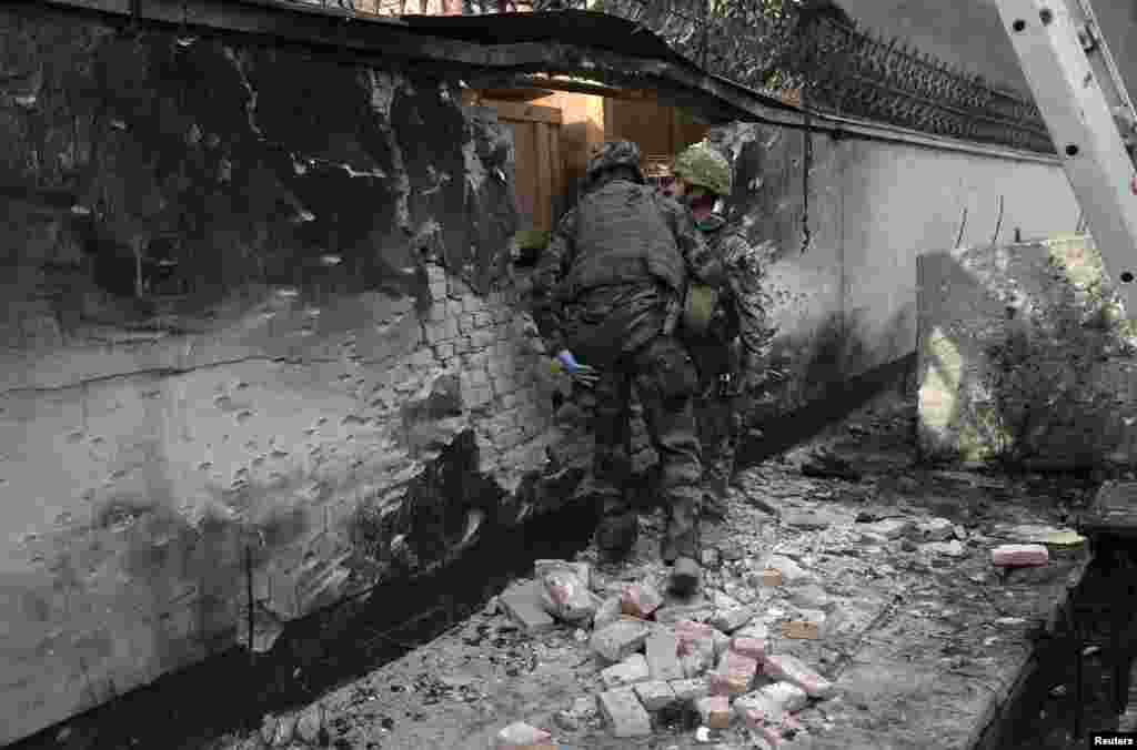 NATO troops inspect the site of a suicide bomb attack in Kabul, Afghanistan, November 21, 2012.
