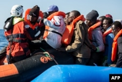 A group of 47 migrants is helped by a Sea-Watch 3 crew member, left, during their transfer from a rescued inflatable boat onto a Sea-Watch 3 RHIB (Rigid Hull Inflatable Boat) during a rescue operation by the Sea-Watch 3 off Libya's coasts, Jan. 19, 2019.