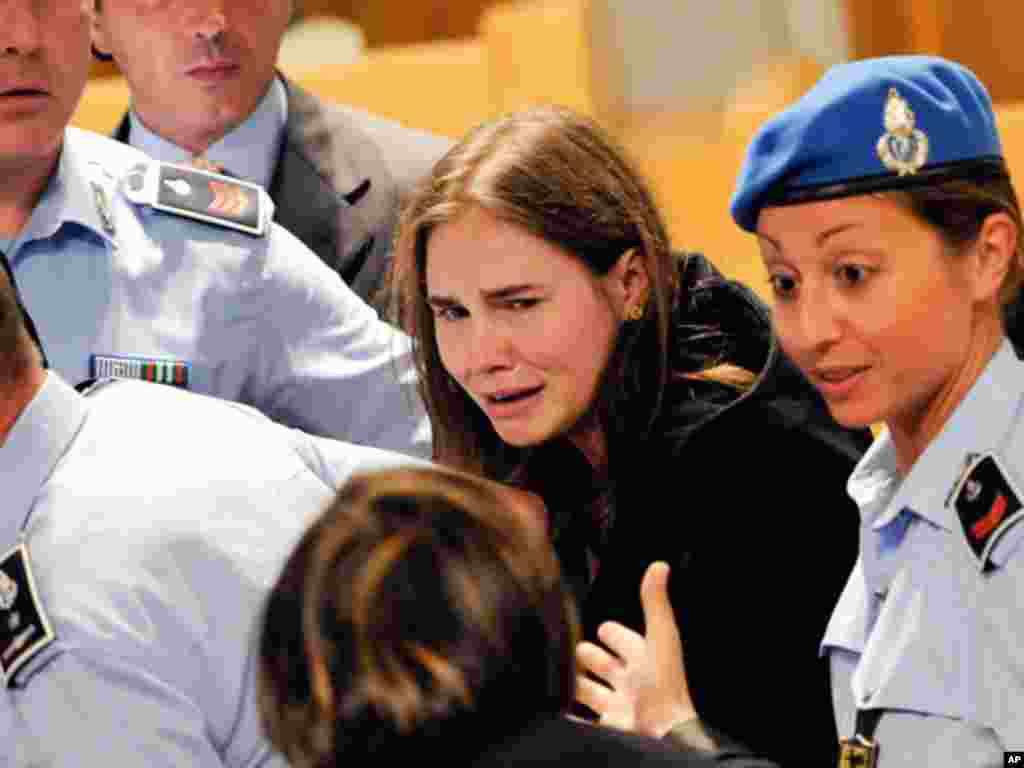 Amanda Knox cries following the verdict that overturns her conviction and acquits her of murdering her British roomate Meredith Kercher, at the Perugia court, Italy, Monday Oct. 3, 2011. An Italian appeals court has thrown out Amanda Knox's murder convict