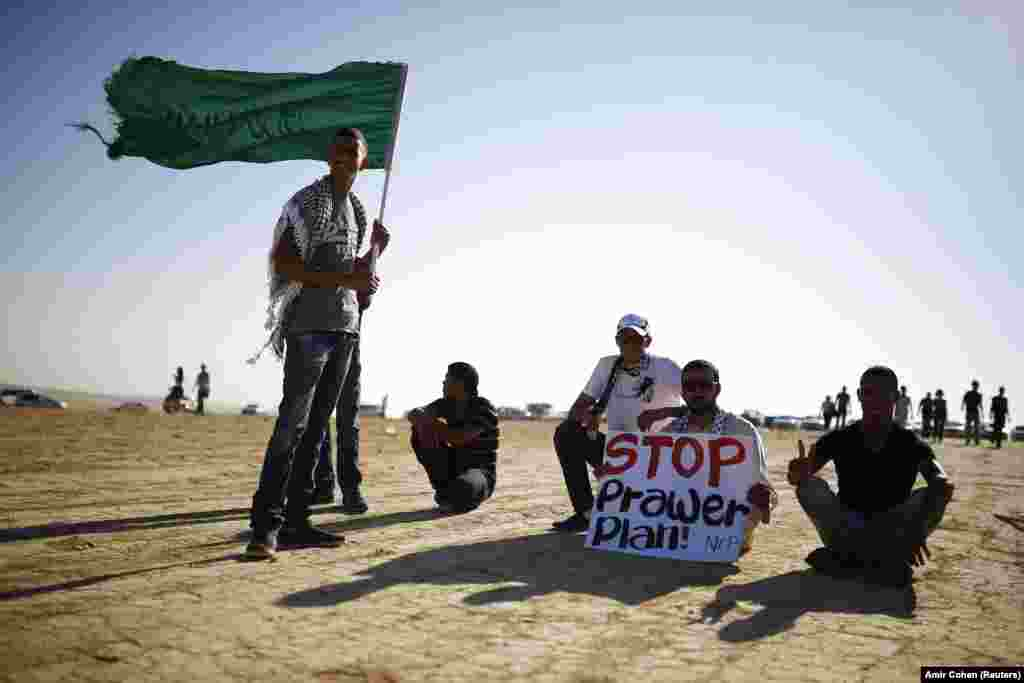 A protester holds a placard as another holds an Islamic movement flag during a demonstration to show their solidarity with Bedouin citizens, near the Bedouin townof Rahat in southern Israel August 1, 2013.