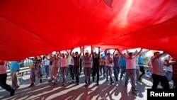 土耳其总理埃尔多安的支持者6月16日在伊斯坦布尔举行集会,撑开一面巨大的土耳其国旗。(照片来源:路透社)