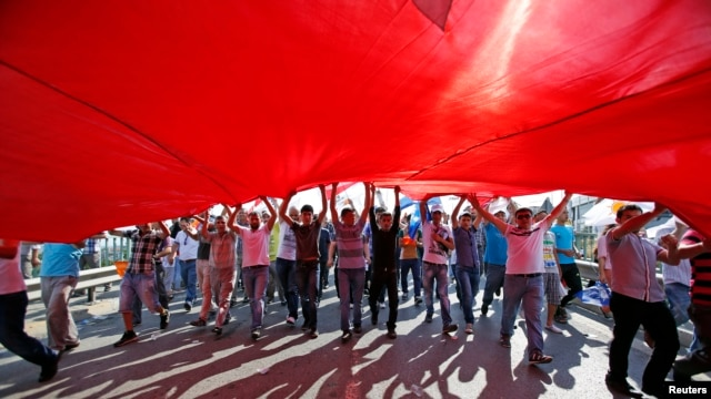 Supporters of Prime Minister Tayyip Erdogan march holding a huge Turkish flag during a rally of ruling AK party in Istanbul Jun. 16, 2013.
