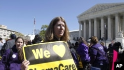 Holding a sign saying 'We Love ObamaCare,' supporters of health care reform rally in front of the Supreme Court in Washington, March 27, 2012.