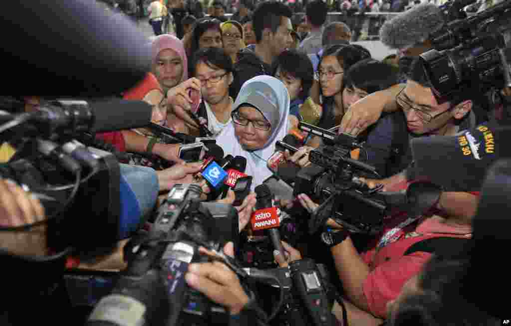 A family member of passengers aboard a missing Malaysia Airlines plane is mobbed by journalists at Kuala Lumpur International Airport in Sepang, outside Kuala Lumpur.