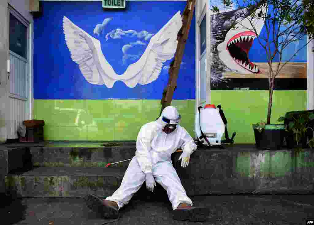 A health worker rests after disinfecting a public restroom at a bus station in Bandung, West Java, Indonesia.
