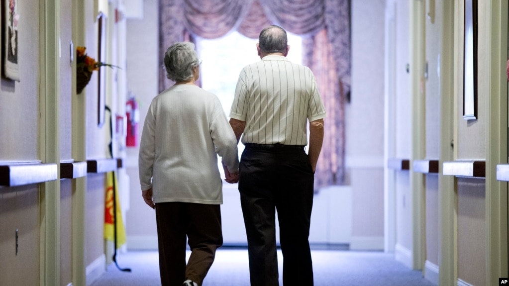 In this Nov. 6, 2015 file photo, an elderly couple walks down a hall in Easton, Pa. Research released on Friday, Nov. 1, 2019 suggests many American adults inaccurately estimate their chances for developing dementia and do useless things to prevent it.