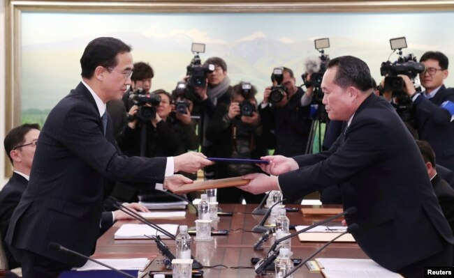 Head of the North Korean delegation, Ri Son Gwon exchanges documents with South Korean counterpart Cho Myoung-gyon after their meeting at the truce village of Panmunjom