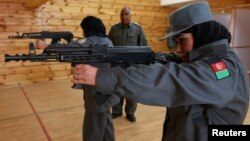 Afghan policewomen aim their guns during shooting exercises at the Afghan National Police Academy shooting range, in Kabul, December 9, 2012.