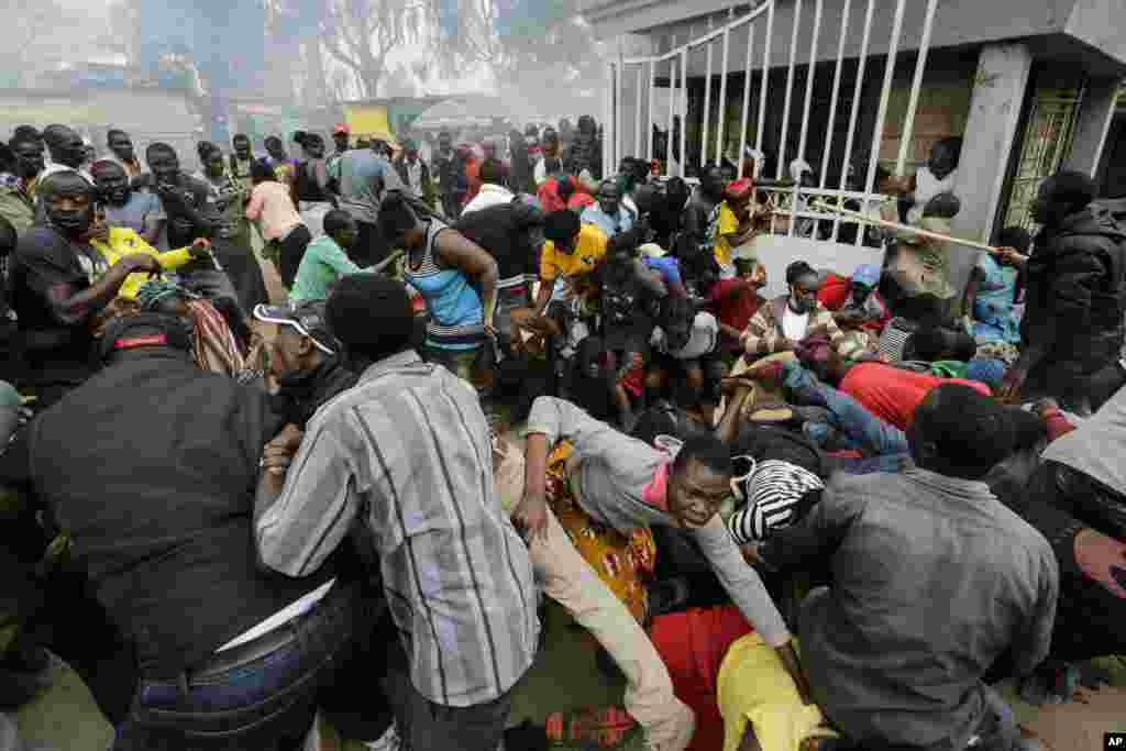 Residents desperate for a planned distribution of food for those suffering under Kenya's coronavirus-related movement restrictions push through a gate and create a stampede, at a district office in the Kibera slum of Nairobi.