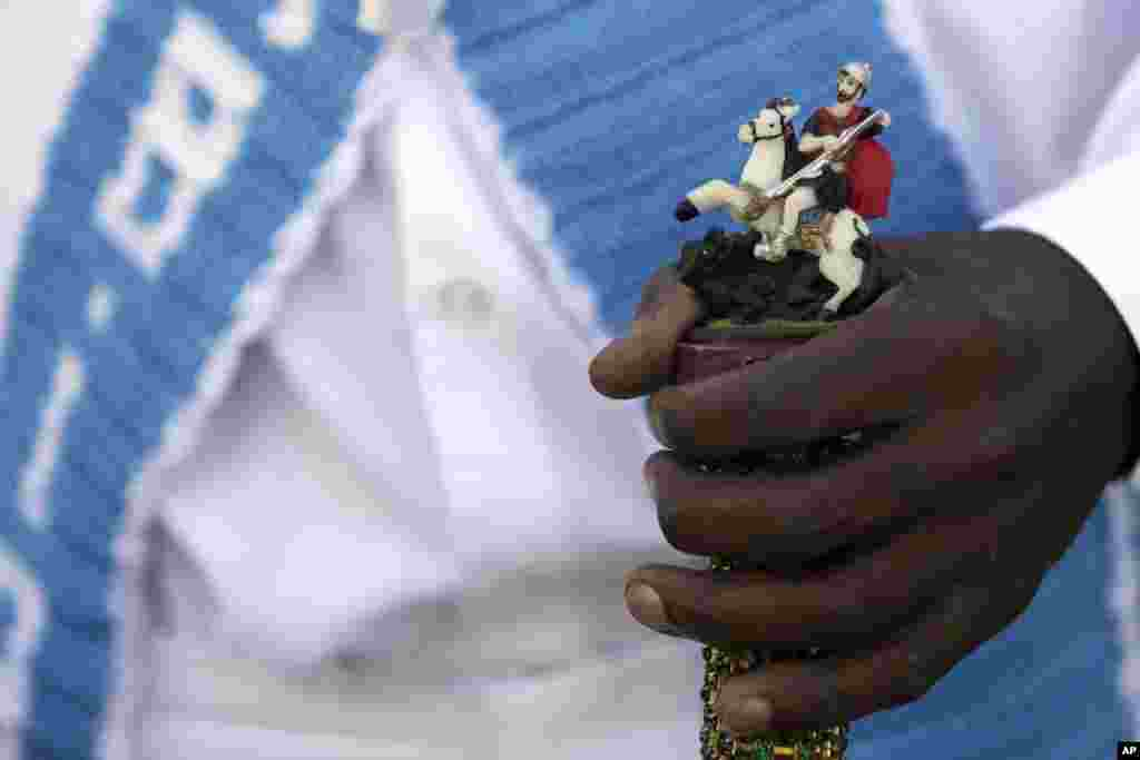 A man holds a walking cane decorated with a statue of St. George during an annual Afro-Christian dance tradition called Congada, in Catalao, Goias state, Brazil, Oct. 9, 2016. St. George is one of the most important and popular saints in Brazilian, and is