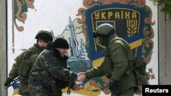 Tentara Ukraina (kedua dari kiri) bersalaman dengan seorang pria bersenjata, yang diyakini merupakan tentara Rusia di markas militer di desa Perevalnoye dekat Simferopol, Krimea. (Reuters/David Mdzinarishvili)