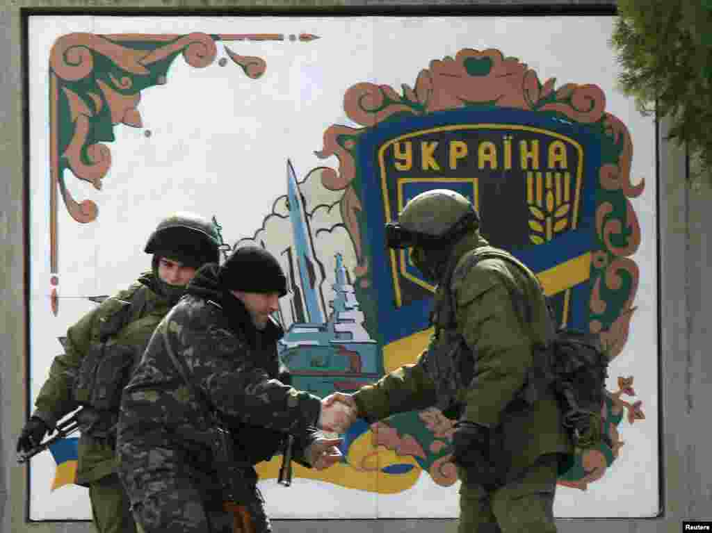 Ukrainian serviceman (2nd L) shakes hand with an armed man, believed to be Russian serviceman, at the Ukrainian military base in the village of Perevalnoye near the Crimean city of Simferopol. Crimea's pro-Russian prime minister will give people living there the choice of taking Russian or Ukrainian passports if the Ukrainian territory becomes part of Russia in a March 16 referendum.