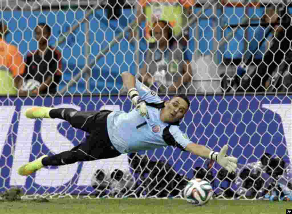 Costa Rica's goalkeeper Keylor Navas dives trying to save a penalty kick during penalty kicks at the World Cup quarterfinal soccer match between the Netherlands and Costa Rica at the Arena Fonte Nova in Salvador, Brazil, Saturday, July 5, 2014. The Nether