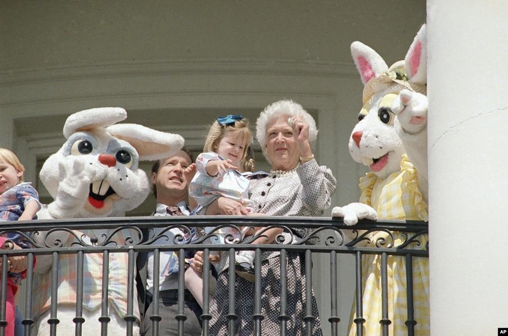 1989年3月27日,第一夫人芭芭拉布什抱著孫女馬歇爾·布什,和兒子尼爾·布什一起站在華盛頓的白宮陽台上,兩側是複活節兔子。
