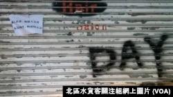 上水一間店舖落閘暫停營業,鐵閘上貼上反對反水貨客示威的標語。(北區水貨客關注組網上圖片)