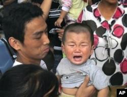 一名因食用毒奶粉而患病等候做超声波检查的儿童在哭泣(资料照片)
