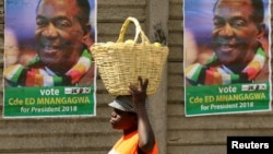 FILE - A street vendor carries fruit while passing campaign posters of President Emmerson Mnangagwa's ruling ZANU-PF party, in Mutare, Zimbabwe, May 19, 2018.