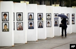 FILE - A woman looks at caricatures of the victims of the sunken ferry Sewol outside a group memorial altar in Ansan, South Korea, Thursday, April 16, 2015. Tears and grief mixed with raw anger Thursday as black-clad relatives mourned the 300 people, mostly high