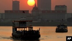 FILE - Ferries transport villagers, students and civil servants from Phnom Penh to Arey Ksat across the Mekong River as the sun sets in Phnom Penh, Cambodia, Saturday, Jan. 31, 2015. (AP Photo/Heng Sinith)
