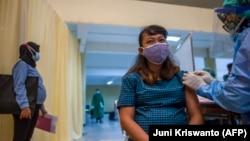 Seorang ibu hamil menerima vaksin Sinovac di Surabaya, 19 Agustus 2021, saat program percepatan vaksinasi. Pemprov Gorontalo mencanangkan vaksinasi COVID-19 bagi 7.326 ibu hamil di wilayah itu.(Foto: AFP/Juni Kriswanto)