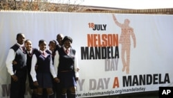 A group of schoolchildren pose near a banner announcing Mandela Day at the Nelson Mandela Foundation in Johannesburg, July 17, 2011