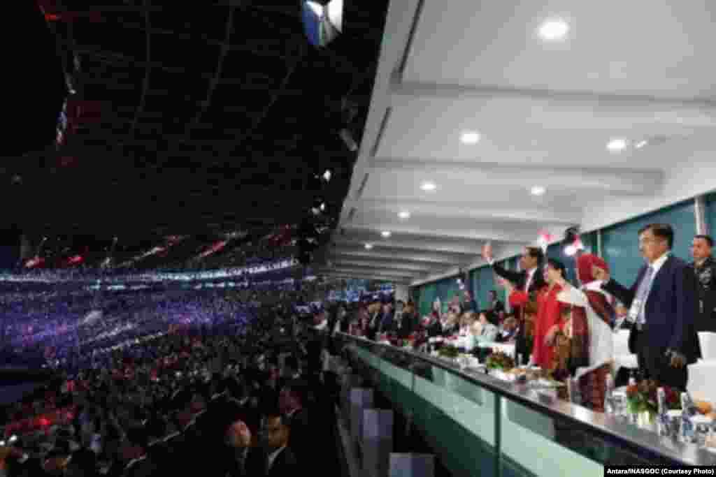 Presiden Joko Widodo (keempat kanan) didampingi Ibu Negara Iriana Joko Widodo (ketiga kanan) dan Wakil Presiden Jusuf Kalla (kanan) didampingi istri, Mufidah Jusuf Kalla (kedua kanan) melambaikan tangan pada Upacara Pembukaan Asian Games ke-18, 18 Agustus 2018.(Photo: Antara/INASGOC/Puspa Perwitasari)