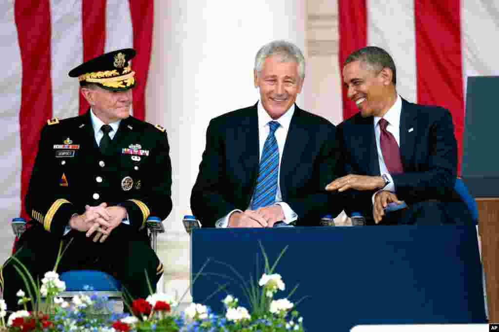 President Barack Obama talks with Secretary of Defense Chuck Hagel, center, and Chairman of the Joint Chiefs of Staff Gen. Martin Dempsey, left, at Arlington National Cemetery in Arlington, Virginia, May 27, 2013.