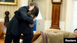 President Barack Obama hugs Dallas nurse Nina Pham as her mother Diane looks on, Oval Office, Washington, Oct. 24, 2014.