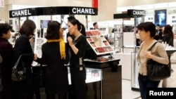Customers choose cosmetics at a cosmetics counter at the Shinsegae department store in Seoul.