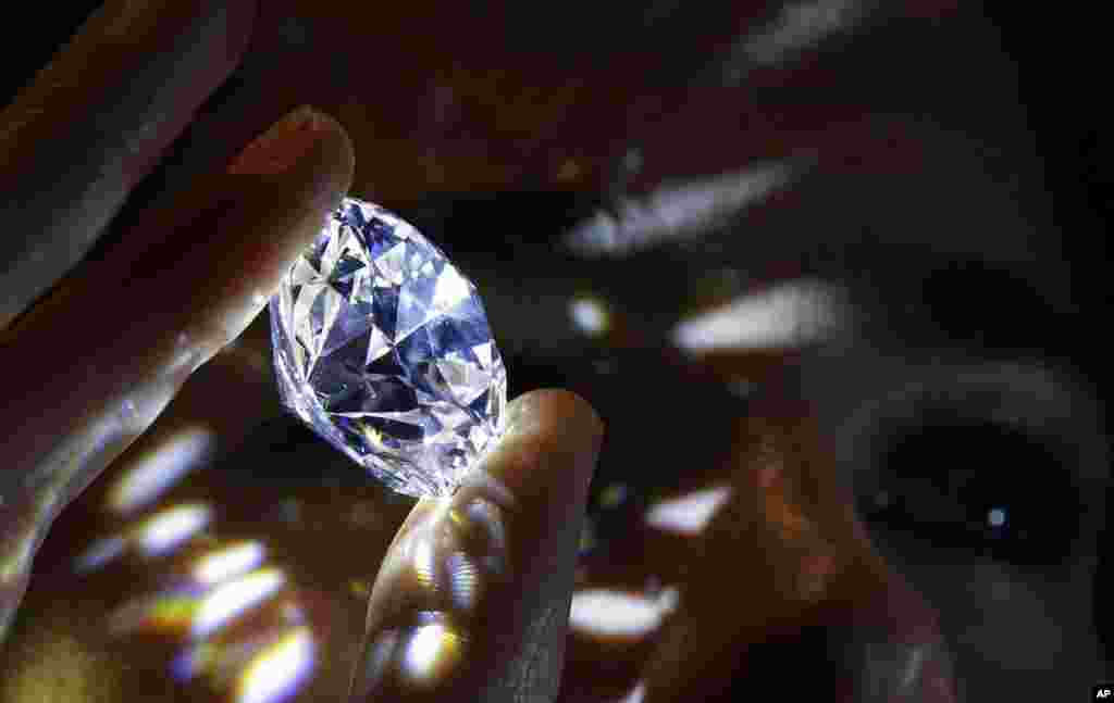 "A 102.34-carat white diamond held is displayed at Sotheby's auction house in London. The diamond is the world's largest known round brilliant diamond to have achieved ""perfection in all critical criteria - Color, Clarity, Cut and Carat."" It is expected to sell for over $33.7 million by private sale in London."