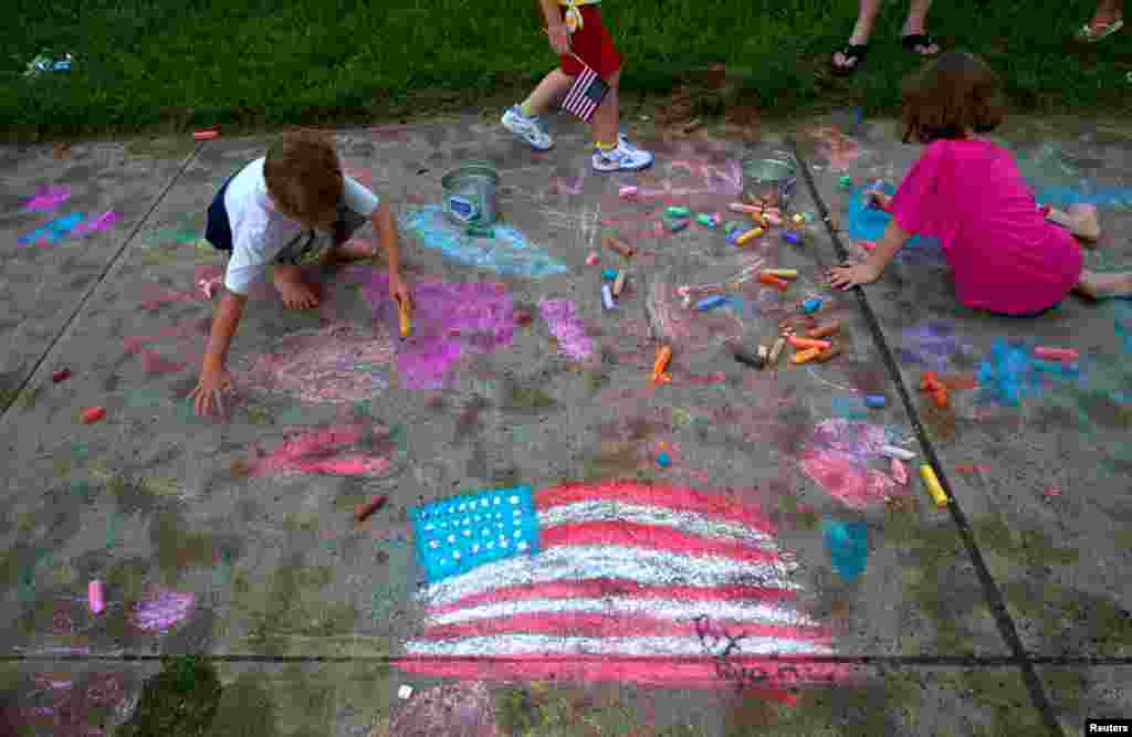 Children draw on the sidewalk during an Independence Day party in Union Beach, New Jersey, July 3, 2013.
