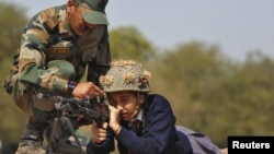 FILE - An Indian army soldier shows the functions of a gun to a schoolgirl during an awareness programme to attract youth in joining the armed forces on the eve of India's Republic Day at Gandhinagar, in the western state of Gujarat, India, Jan. 25, 2016.