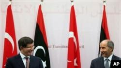 土耳其外交部長達烏特奧盧(左)星期二和利比亞過渡政府領導人賈利勒在班加西的一個記者會上會面。達烏特奧盧表示北約仍然繼續行動﹐直至利比亞局勢穩定。