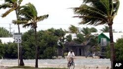 A cyclist rides his bike in Key West, Florida, Sunday, Aug. 26, 2012. Tropical Storm Isaac gained fresh muscle Sunday as it bore down on the Florida Keys, with forecasters warning it could grow into a dangerous Category 2 hurricane as it nears the norther