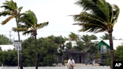 Seseorang mengendarai sepeda di kawasan Key West, Florida sementara angin bertiup kencang menjelang datangnya badai Isaac, Minggu (26/8).