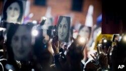 İnsanlar qətlə yetirilmiş jurnalist Dafne Karuana Qalizianın şəkillərini nümayiş etdir
