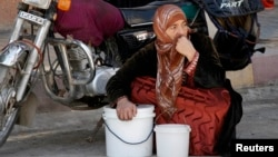 A woman squats next to her buckets as she waits for her turn to receive a free meal from a soup kitchen in the city of Raqqa, eastern Syria, Oct. 7, 2013.