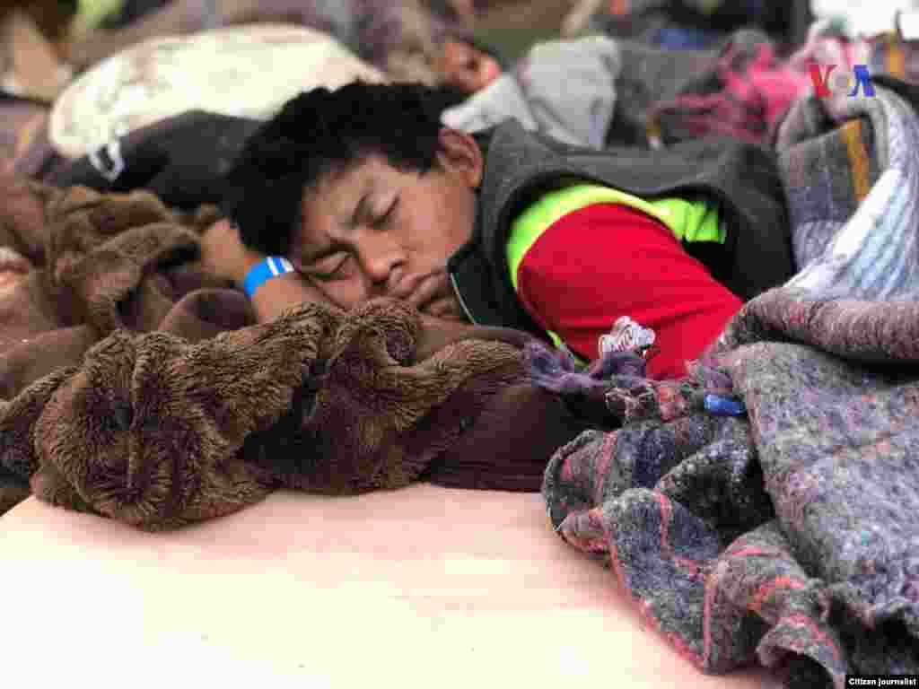 Una persona duerme sobre unas cobijas en el piso, en un albergue en México. Fotografía: Celia Mendoza- VOA