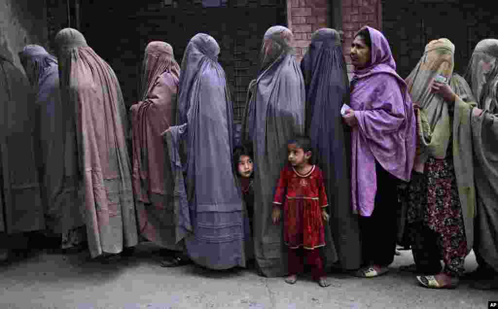 Women line up to enter a polling station and cast their ballots, on the outskirts of Islamabad, May 11, 2013.