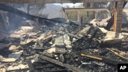 The remains of a burned home smoulder in Iron Canyon Road area near Santa Clarita, California, on Sunday, July 24, 2016.