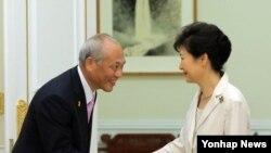 박근혜 한국 대통령(왼쪽)이 25일 청와대를 예방한 마스조에 요이치 도쿄도지사와 악수하고 있다.