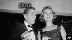 Humphrey Bogart ພ້ອມດ້ວຍພັນລະຍາ Lauren Bacall ໄດ້ໄປຮ່ວມ ພິທີເປີດໂຕຮູບເງົາ Hollywood 'The Desperate Hours' ຮອບປະຖົມມະເລີກ ເມື່ອວັນທີ 12 ຕຸລາ 1955.